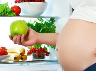 Kobieta w ciąży stoi przy lodówce i trzyma w ręku jabłko