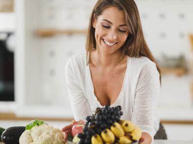 Młoda kobieta patrzy na miskę z owocami. Obok na blacie kuchennym leżą warzywa.