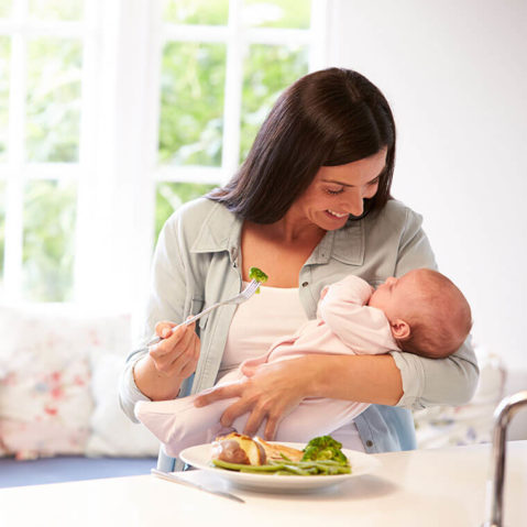 Młoda mama trzyma dziecko na rękach, do którego uśmiecha się. Kobieta jest w trakcie jedzenia obiadu.