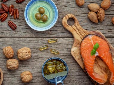 Oliwki, surowy łosoś, orzechy włoskie leżą na drewnianym stole