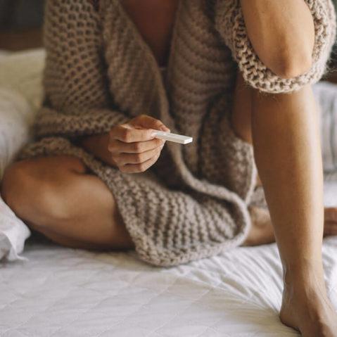 Kobieta na łóżku z testem ciążowym