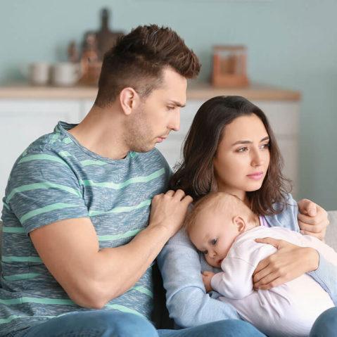 Zamyśleni rodzice siedzą z dzieckiem na rękach na kanapie