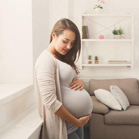 Kobieta w ciąży opiera się o parapet. Dłonie ma ułożone na brzuchu.