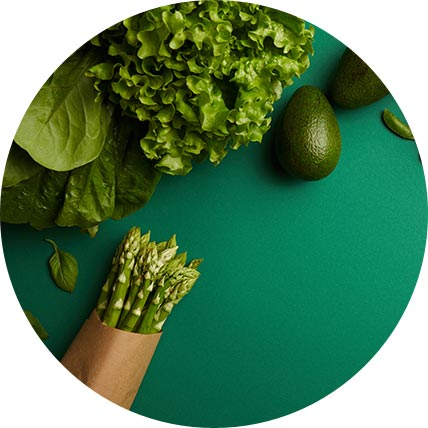 Zielone warzywa i owoce: awokado, szparagi, groszek, szpinak i sałata na zielonym materiale.