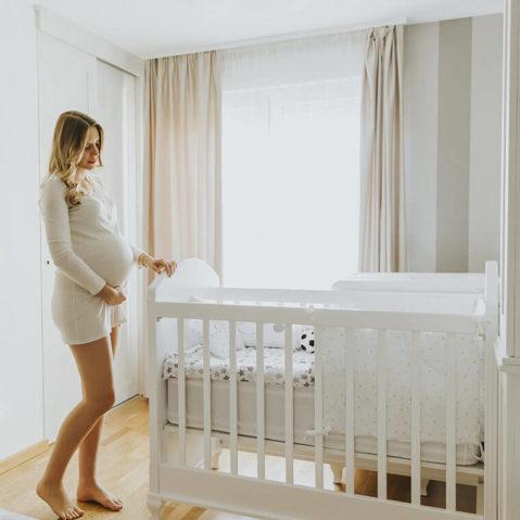 Kobieta w ciąży przy łóżku dla dziecka