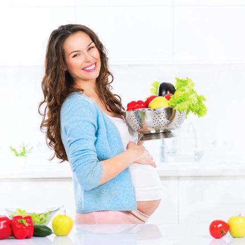 Uśmiechnięta kobieta w ciąży trzyma owoce i warzywa w durszlaku