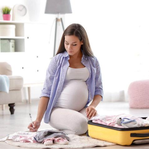 Kobieta w ciąży siedzi na podłodze i pakuje dziecięce ubranka do walizki