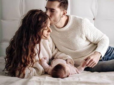 Młoda para leży na łóżku. Między nimi leży niemowlak. Mężczyzna całuje kobietę w czoło z czułością.